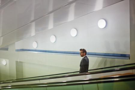 descending: Young businessman standing on descending escalator Stock Photo