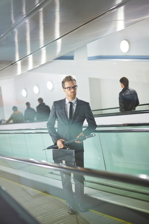 ascending: Serious businessman with briefcase and umbrella ascending on escalator