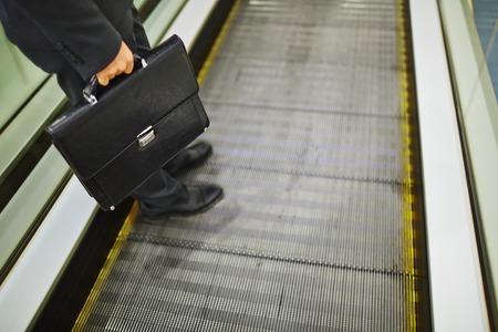 descending: Close-up of legs of businessman with briefcase descending on escalator