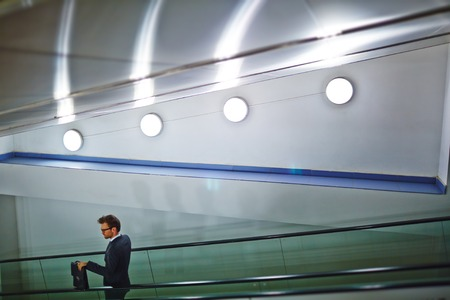 downstairs: Young businessman with briefcase moving downstairs on escalator Stock Photo