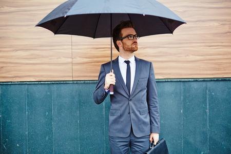 lloviendo: Joven empresario con maletín de pie fuera bajo el paraguas