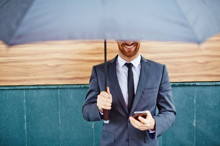 uomo sotto la pioggia: Sorridente imprenditore con cellulare in piedi sotto l'ombrello