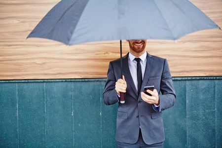 proteccion: Empresario joven feliz con el teléfono inteligente de pie bajo el paraguas