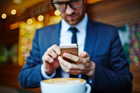 career young: Young businessman writing sms in cafe Stock Photo