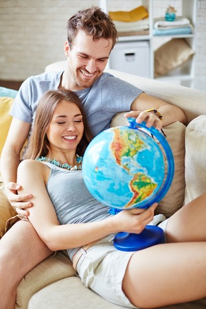 amorous woman: Happy couple with globe choosing where to spend vacations