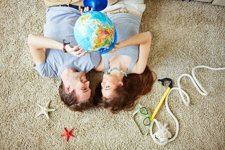 restful: Restful couple with globe looking at one another while lying on the floor Stock Photo