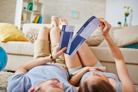 restful: Restful couple with air tickets lying on the floor at home Stock Photo