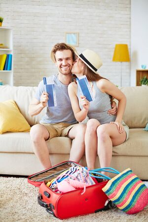 Happy couple with air tickets sitting on sofa with suitcase near by