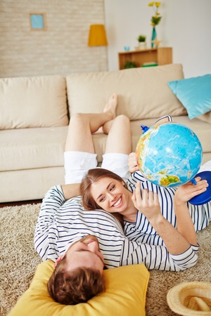 restful: Restful couple with globe discussing where to spend summer while lying on the floor by sofa at home