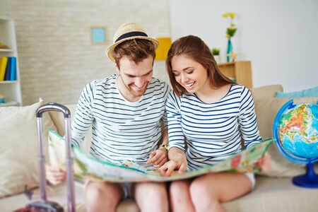 Young couple with map looking at camera at home photo