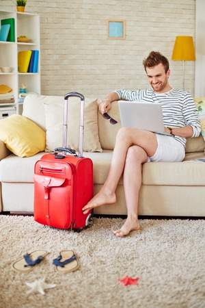 vacation home: Young man browsing in the net while choosing tour
