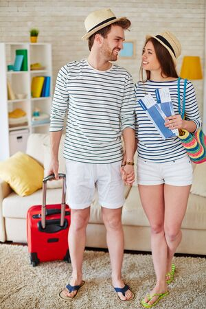 sweethearts: Romantic sweethearts with airtickets and baggage looking at one another