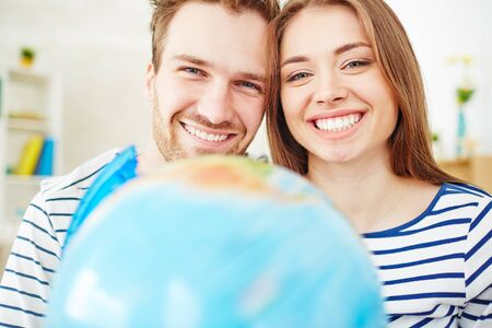 toothy smiles: Amorous couple looking at camera with toothy smiles