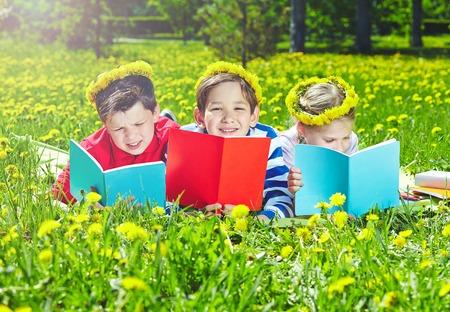 Cute children in dandelion wreaths reading on lawn photo