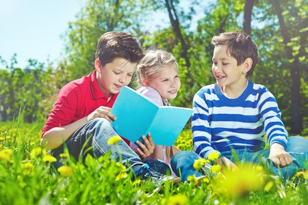Cute children with book reading and talking on lawn photo