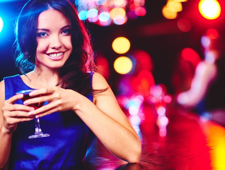 adult entertainment: Happy young woman with glass of martini looking at camera Stock Photo
