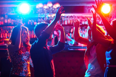 nighttime: Amigos energ�ticos que bailan en club nocturno