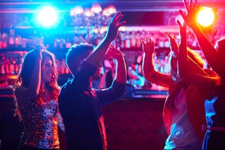 clubs: Energetic friends dancing in night club