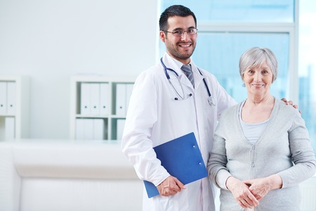 clinician: Smiling doctor with clipboard and elderly female patient in clinic