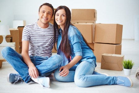 settler: Happy couple looking at camera while sitting on the floor of new flat Stock Photo
