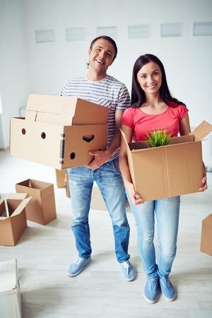 pareja en casa: Colonos felices con los paquetes de pie en su nueva casa