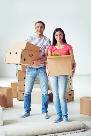 settler: Young man and woman holding packages with domestic things