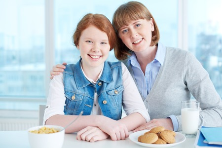 teenage girl: Cute teenage girl and her mother having breakfast Stock Photo