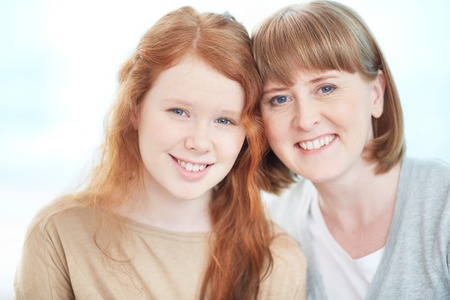smiling teenagers: Mature woman and her pretty teenage daughter