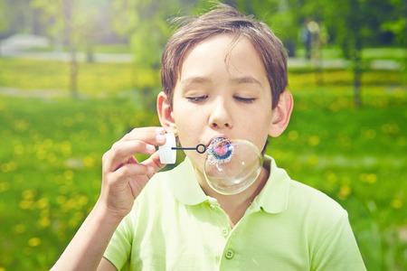 Handsome boy blowing soap bubbles in park photo