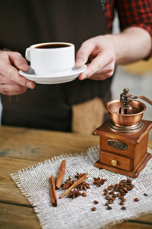 flavorings: Barista holding cup of black coffee over table with coffee grinder, coffee grains and aromatic flavorings