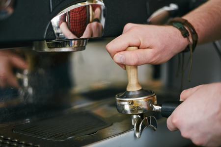 tamper: Hands of barista grinding coffee beans in tamper Stock Photo