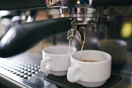 cups of coffee: Black coffee pouring in two porcelain cups in coffee machine Stock Photo