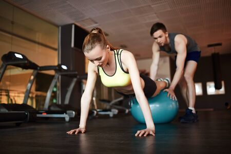 activewear: Girl in activewear doing push ups on ball with help of trainer