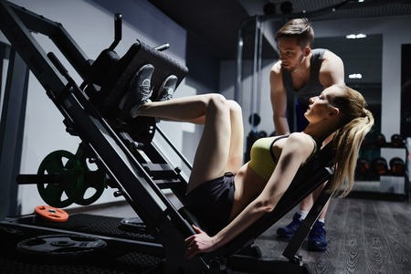 activewear: Fit woman doing exercise for legs on facilities with trainer near by Stock Photo