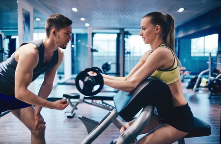 arm muscles: Young woman strengthening arm muscles in gym Stock Photo