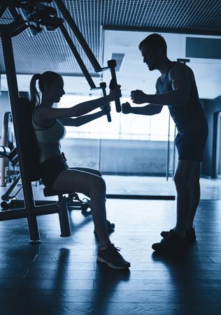 fitness hombres: Contornos de mujer activa que ejercita en las instalaciones y su entrenador en el gimnasio