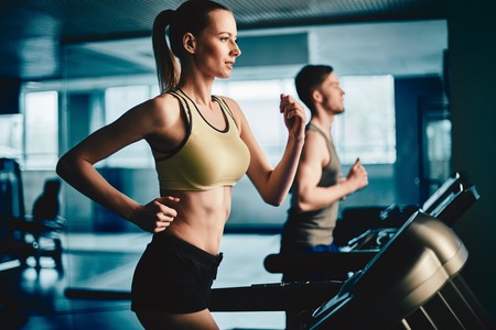 Active female running on treadmill in gym with young man on background