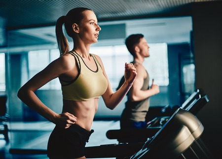 Active young woman and man running on treadmill in gym