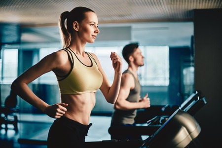 gym: Pretty woman running on treadmill with fit young man on background Stock Photo