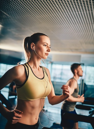 Active woman listening to music while running on treadmill Stock Photo