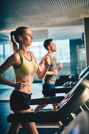 Fit girl with earphones running on treadmill and listening to music with guy on background