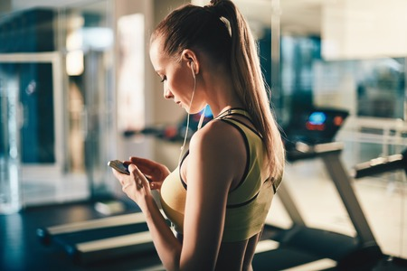 Actief meisje met smartphone luisteren naar muziek in sportschool