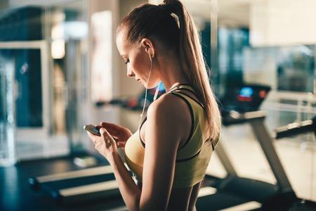 escucha activa: Muchacha activa con el teléfono inteligente escuchar música en el gimnasio Foto de archivo