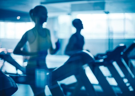 treadmill: Young man and woman running on treadmills in gym Stock Photo