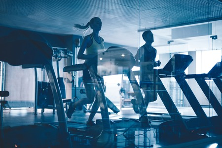 workout gym: Active young people running on treadmills in sports club
