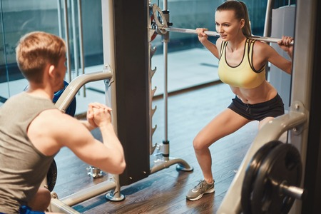 Young woman lifting weight and looking at her trainer in gym Stock Photo - 41624227