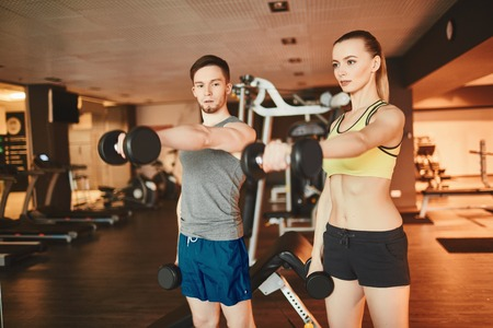 stretched: Young man and woman with stretched arms exercising barbells together