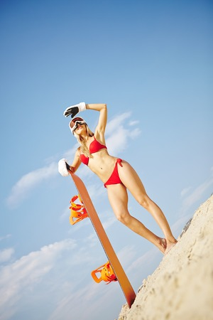 Beautiful girl with sandboard standing on sandy beach photo