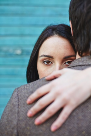 couples hug: Pretty female looking at camera out of man back while embracing him
