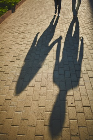 amorous: Shadows of amorous dates walking down trottoire Stock Photo